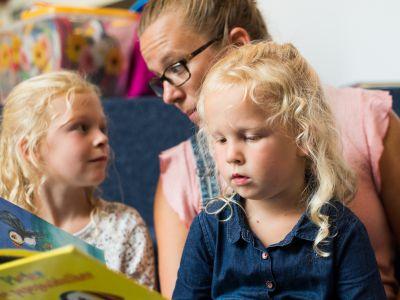 supervoorlezer en leerling van de Waterval Levy van Nobelen  leest voor in de bibliotheek